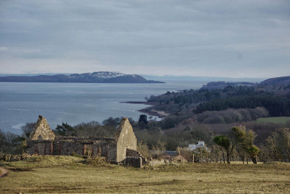 Old Cottage with the farmhouse roof beyond and views over the Firth of Clyde in the background